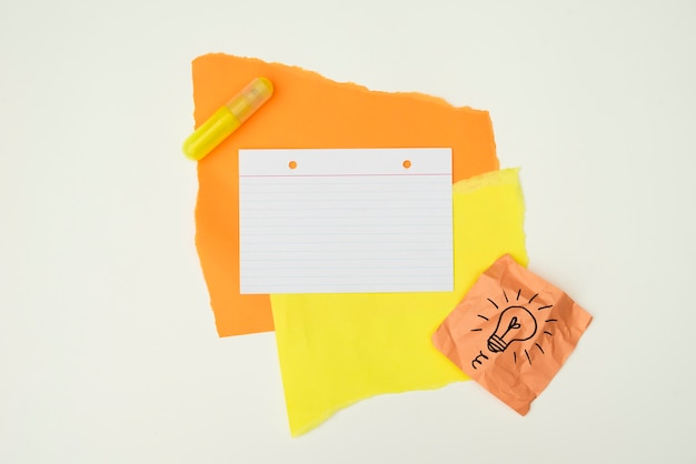 Kleur papier en lijm met hand getrokken gloeilamp notitie papier geïsoleerd op een witte achtergrond