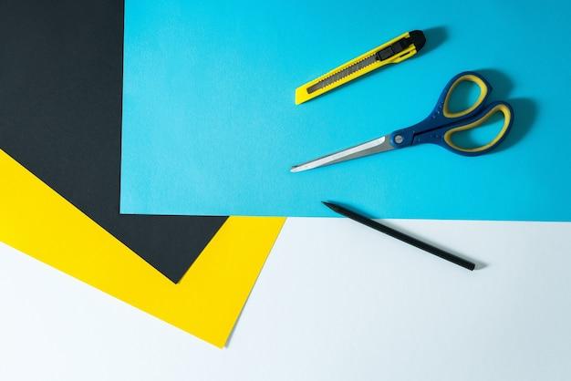 Kleur papieren achtergrond met pen, schaar en papier mes bovenop.