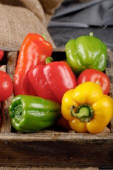 Kleur paprika in een rustieke lade met waterdruppels op hen.
