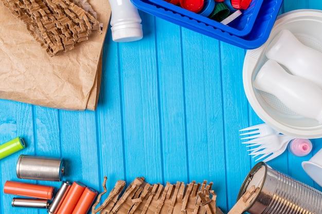Kleur plastic, metalen blikjes, papier, kartonafval op blauwe achtergrond met kopie ruimte