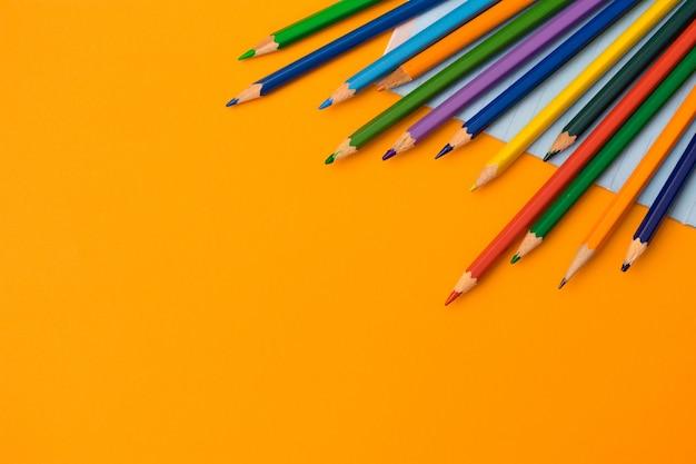 Kleur potloden en het voorbeeldenboek op de oranje achtergrond. terug naar school concept plat lag.