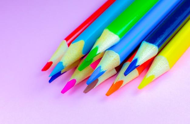 Kleur potloden liggend op roze achtergrond. detailopname. terug naar schoolconcept. kleurrijk kunststudie- en schilderproces. tekenen met potloden. kopieer de ruimte voor een ansichtkaartwens.
