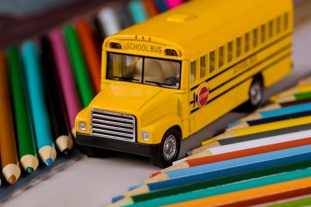 Kleur potloden op gele schoolbus schoolbenodigdheden