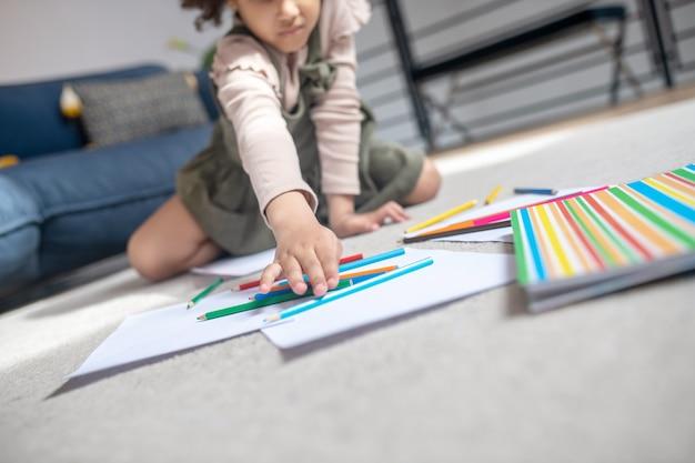 Kleur selectie. hand van een klein meisje met een donkere huid dat op de vloer zit en zich uitstrekt en kleurpotlood kiest dat met vellen papier ligt