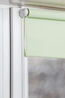 Kleur verduisterend rolgordijn op het witte kunststof venster. luiken op het plastic raam.