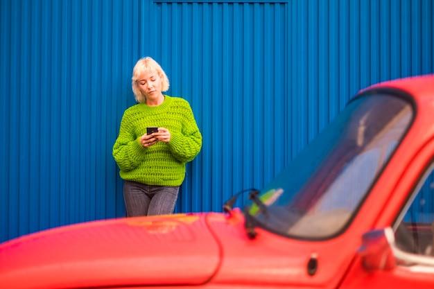 Kleuren en alternatieve gelukkige levensstijl concept afbeelding met blonde aantrekkelijke vrouw dertig jaar oud met behulp van mobiele telefoon internettechnologie buiten de rode auto en met blauwe muur