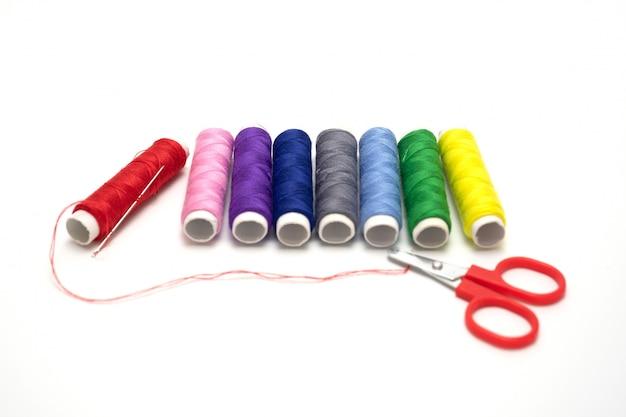 Kleuren naaiende draden die op witte achtergrond worden geïsoleerd.