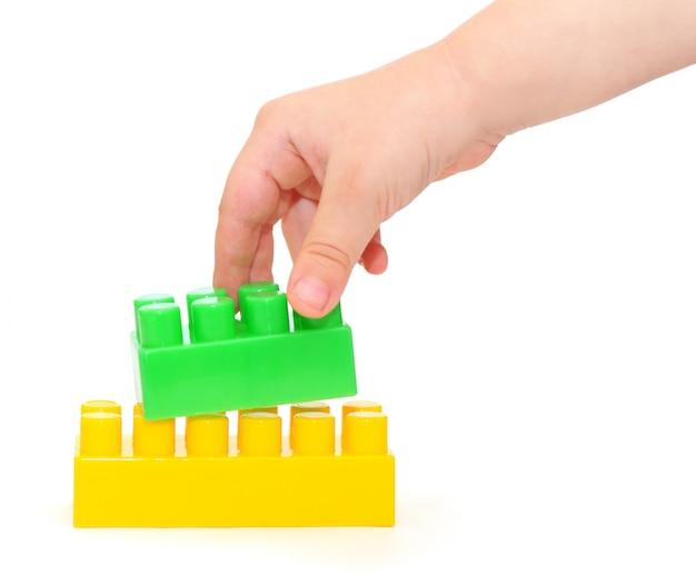 Kleuren plastic blokken met hand die op wit wordt geïsoleerd