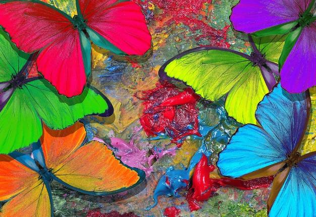 Kleuren van de regenboog. kleur concept. heldere tropische morphovlinders op het palet van een kunstenaar. kunst verven en vlinders kleurrijke tafel