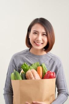 Kleurenafbeelding met horizontale oriëntatie van een vrouw met een papieren zak vol groenten / groenten aan je dieet toevoegen