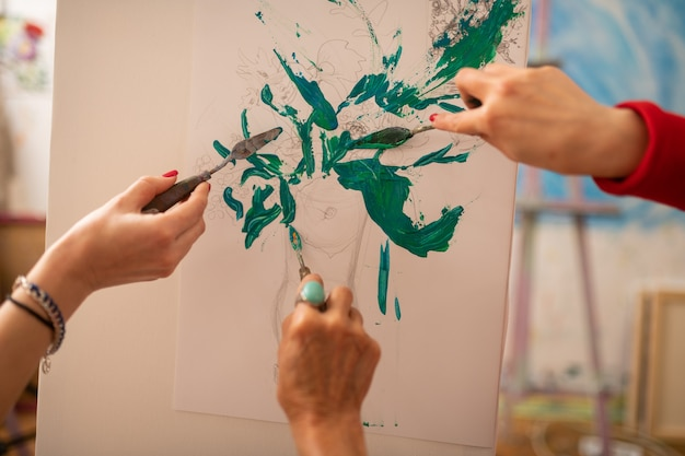Kleurende vaas. drie kunstenaars kleuren vaas met planten en bloemen met groene gouache