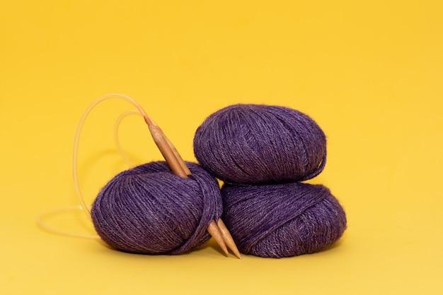 Kleurendraad voor het breien, gebreide sjaal, breinaalden op een donkere achtergrond.