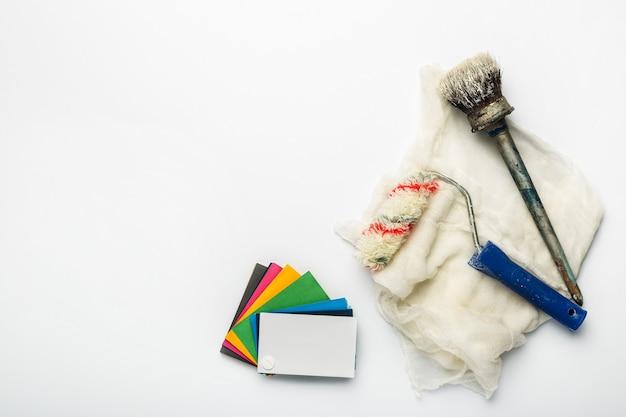 Kleurenpalet met tinten verf, penselen en rollers op een wit