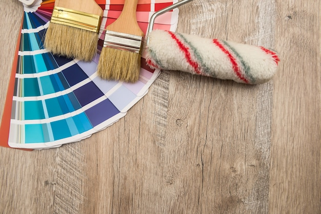 Kleurenpaletgids en kwastroller op houten bord