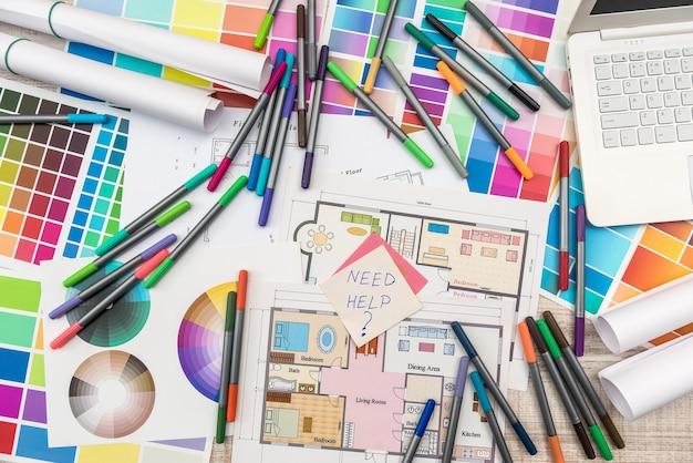 Kleurenpaletten met huisplan op het bovenaanzicht van het bureau. ontwerper werkt bij nieuw project
