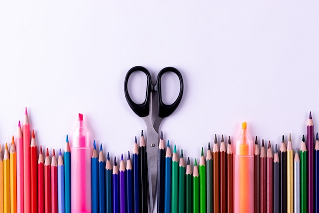 Kleurenpotloden en kantoorbehoeften op witte lijstachtergrond. terug naar school-concept.