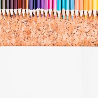Kleurenpotloden geplaatst boven blad van document op cork achtergrond