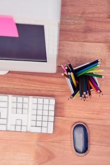Kleurenpotloden in kruik door computer bij houten bureau
