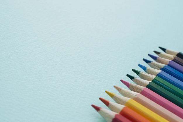 Kleurenpotloden op een blauwe achtergrond. potloden om te tekenen.