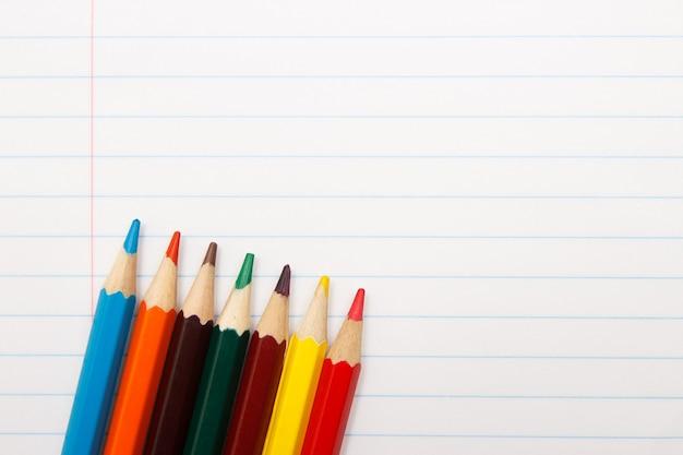 Kleurenpotloden op een notitieboekje. onderwijs concept. ruimte kopiëren. bovenaanzicht