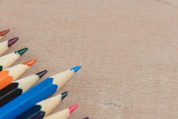 Kleurenpotloden op houten textuurachtergrond