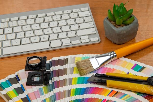 Kleurenschaal met stylus en vergrootglas erop en een notitieboekje
