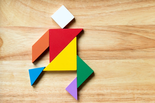 Kleurentrampuzzel in lopende mensenvorm op houten achtergrond