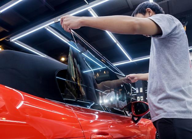 Kleurfolie aanbrengen op een autoruit in een autoservice