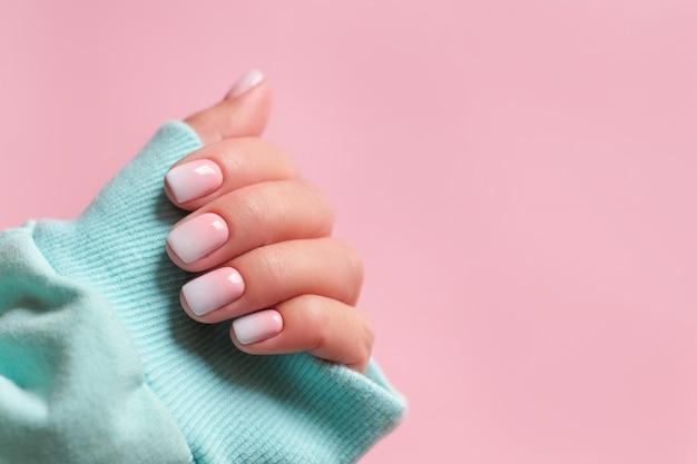 Kleurovergang manicure en handen spa mooie vrouw hand close-up gemanicuurde nagels en zachte handen huid mooie dames nagels met mooie baby boomer manicure roze achtergrond kopie ruimte