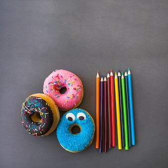 Kleurpotloden die dichtbij donuts liggen