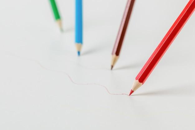 Kleurpotloden die gekleurde lijnen trekken op een witte achtergrond. briefpapier en schoolbenodigdheden.