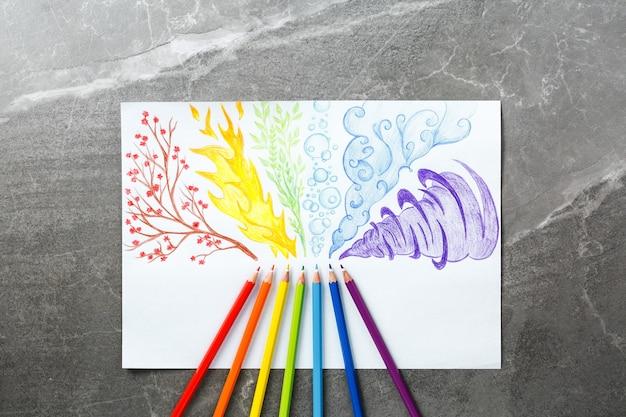 Kleurpotloden die regenboogrook trekken. plat leggen