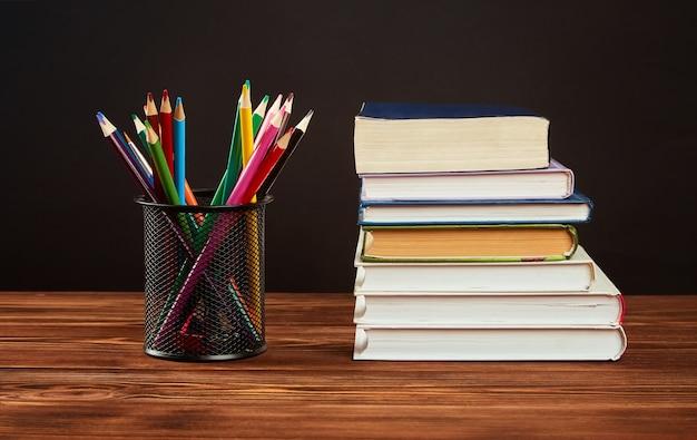 Kleurpotloden, een stapel boeken op een houten tafel.