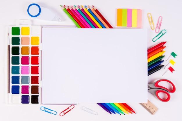 Kleurpotloden en aquarellen op wit, terug naar school, briefpapier met lege ruimte