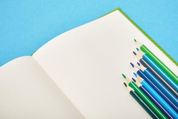 Kleurpotloden en blocnote op blauwe achtergrondexemplaarruimte