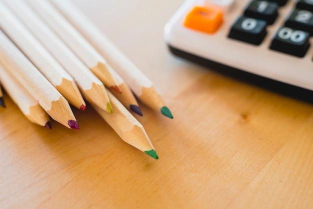 Kleurpotloden en calculator op een tafel.