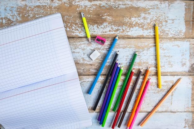 Kleurpotloden en notitieboekjes op een houten lijst