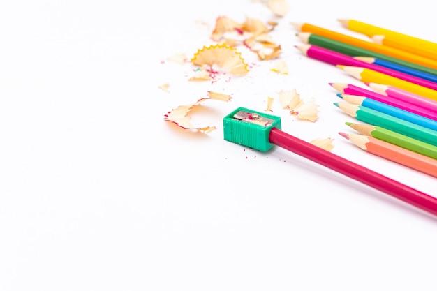 Kleurpotloden en puntenslijper op een witte achtergrond