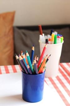 Kleurpotloden en stiften in de standaards op de tafel.