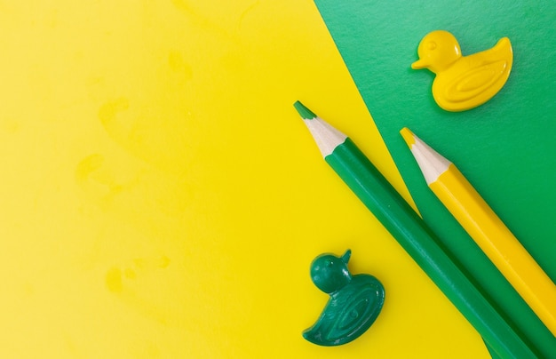 Kleurpotloden geïsoleerd op groene en gele achtergrond close-up