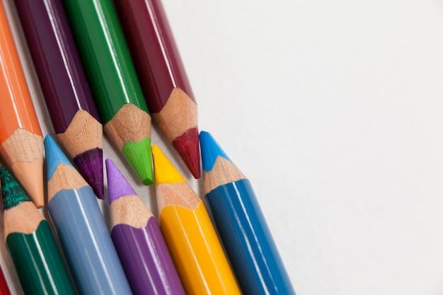 Kleurpotloden gerangschikt in koppelingspatroon op witte achtergrond