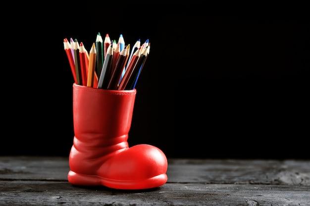 Kleurpotloden in een rode laars