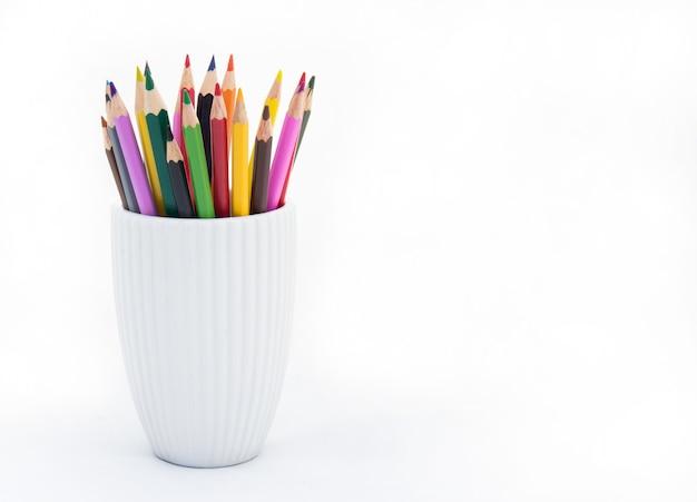 Kleurpotloden in een wit glas op een witte achtergrond