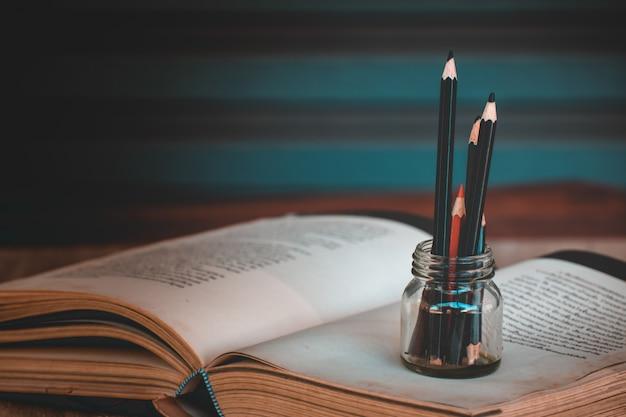 Kleurpotloden in glazen flessen op boeken