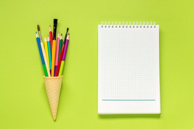 Kleurpotloden in ijsje, notitieboekje op groene achtergrond. concept terug naar school
