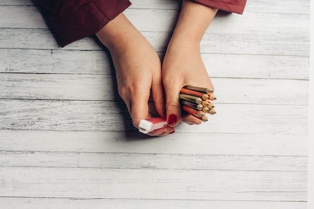 Kleurpotloden in vrouwelijke handen op een houten.