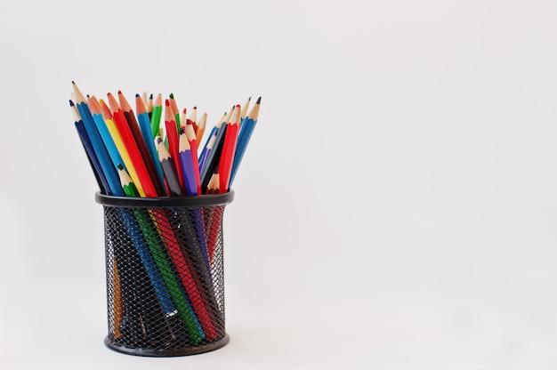 Kleurpotloden in zwart potloodgeval dat op wit wordt geïsoleerd