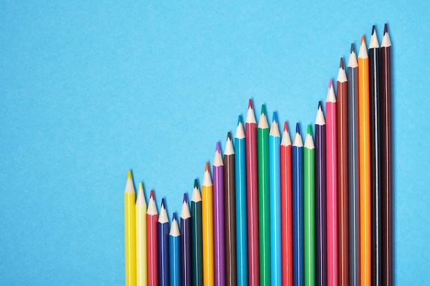 Kleurpotloden liggen in de vorm van een grafiek op een blauwe achtergrond bovenaanzicht kopie ruimte