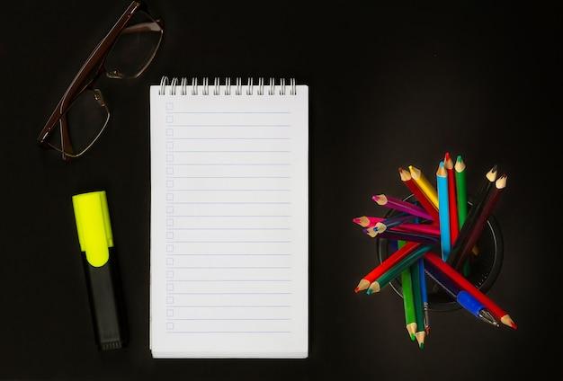 Kleurpotloden, marker, glazen en kladblok op een zwarte achtergrond. uitzicht van boven.