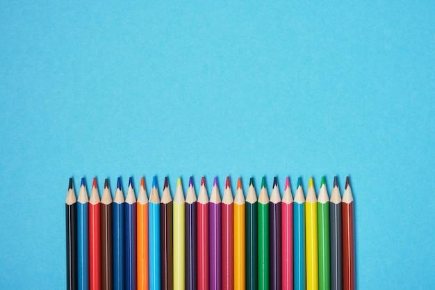 Kleurpotloden op blauwe achtergrond kopie ruimte bovenaanzicht